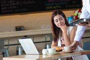 asiatisches Mädchen, das an einem Kaffeehaus mit einem Laptop arbeitet foto