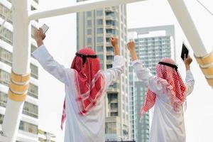 Araber und Geschäftsmann stehen und heben beide Hände hoch foto