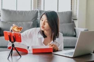 Frau Food Blogger essen Pizza beim Erstellen eines neuen Inhaltsvideos foto