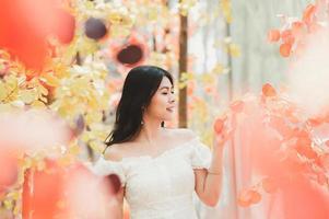 asiatische Frau in einem weißen Kleid im Herbst foto