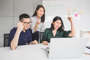 glückliche junge asiatische Geschäftsleute feierten Erfolg foto