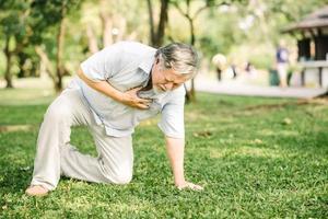 älterer Mann, der Schmerzen fühlt, die unter Herzinfarkt im Freien leiden foto