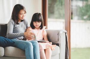 asiatische Mutter und Tochter lesen ein Buch foto