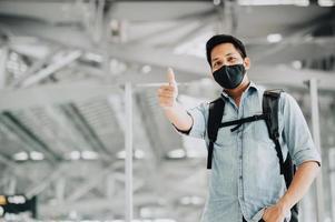 asiatischer Mann mit Maske schützen vor Coronavirus mit Daumen nach oben foto