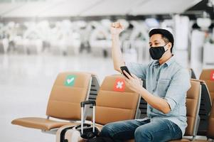 asiatischer Mann, der Gesichtsmaske mit Handy trägt und seinen Arm hebt, um zu feiern foto