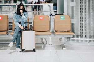 Reisende Frau, die Gesichtsmaske hustet, während sie auf sozialem Distanzierungsstuhl sitzt foto