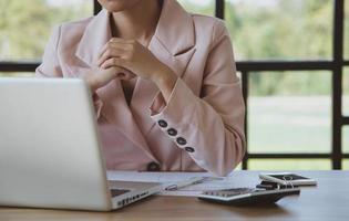 junge Geschäftsfrau, die am Laptop in ihrer Arbeitsstation arbeitet foto