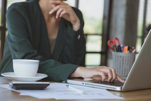 junge Geschäftsfrau, die am Laptop an ihrem Arbeitsplatz arbeitet foto
