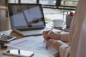junge Geschäftsfrau, die am Laptop im Büro arbeitet foto