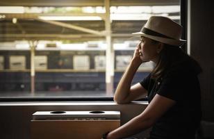 Frau schaut aus dem Zugfenster foto