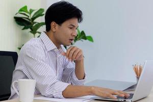 junger Berufstätiger bei der Arbeit gestresst foto
