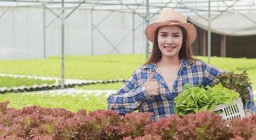 Frau hält einen Korb Salat foto