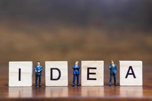 Miniaturmenschen, die mit Holzklötzen mit der Wortidee auf einem hölzernen Hintergrund stehen foto