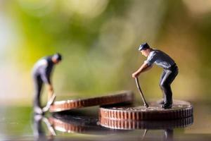Miniaturarbeiter, die Werkzeuge auf Münzen mit einem grünen Bokehhintergrund halten, Konstruktionskonzept foto