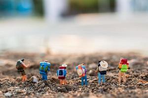 Miniaturreisende mit Rucksäcken Bergsteigen, Wandern und Rucksackwandern im Freien Konzept foto