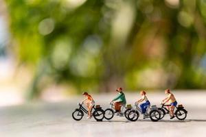 Miniaturmenschen, die Fahrrad draußen im Freien mit einem grünen Bokehhintergrund, Sport- und Reisekonzept fahren foto