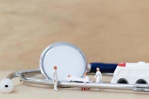 Miniaturärzte mit Krankenschwestern, die einen Patienten auf einer Trage tragen, Gesundheitskonzept foto