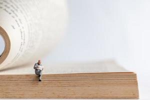 Miniaturgeschäftsmann, der ein Buch über ein altes Buch liest, Geschäftserziehungskonzept foto