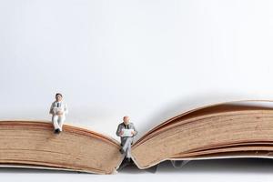Miniaturgeschäftsleute, die ein Buch über ein altes Buch lesen, kaufmännisches Bildungskonzept foto