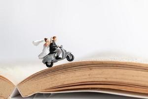 Miniaturpaar, das ein Motorrad auf einem alten Buch fährt, Valentinstagkonzept foto