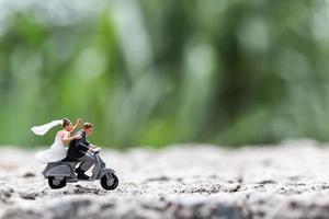 Miniaturpaar, das ein Motorrad auf einem unscharfen Naturhintergrund reitet foto
