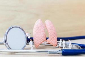 Miniaturärzte und Krankenschwestern, die das Konzept der menschlichen Lunge, des Virus und der Bakterieninfektion beobachten und diskutieren foto
