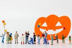Miniaturleute, die Luftballons auf einem weißen Hintergrund mit einer Halloween-Dekoration halten foto