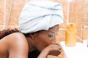 junge Frau, die ihren Mund wäscht foto
