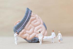 Miniaturärzte und Krankenschwestern, die den menschlichen Darm, die Wissenschaft und das medizinische Konzept beobachten und diskutieren foto