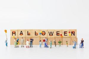 Miniaturleute, die Luftballons mit Holzklötzen mit Text Halloween auf einem weißen Hintergrund halten foto