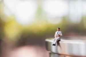 Miniaturgeschäftsmann sitzt und liest ein Buch im Freien, Bildung und Geschäftskonzept foto
