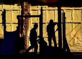Silhouette von zwei Männern, die auf einer Leiter stehen foto