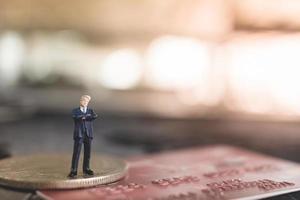 Miniaturgeschäftsmann, der auf einem Münz-, Geschäfts- und Finanzkonzept steht