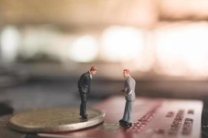 Miniaturgeschäftsleute, die auf einem Münz-, Geschäfts- und Finanzkonzept stehen