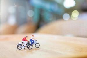 Miniaturmenschen, die auf einer Holzbrücke, Gesundheitskonzept radeln foto