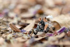 Miniaturpaar, das ein Motorrad in einem Garten fährt foto