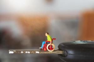 Miniatur behinderter Mann, der in einem Rollstuhl auf einem Autoschlüssel sitzt foto