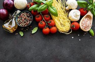 gesunde mediterrane Ernährung, Zutaten für italienisches Essen auf schwarzem Hintergrund foto
