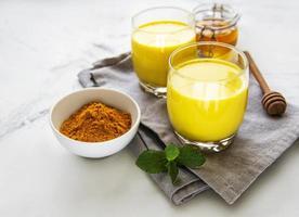 goldene Milch mit Zimt, Kurkuma, Ingwer und Honig über weißem Marmorhintergrund foto