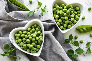 grüne Erbsen in herzförmigen Schalen auf einem Stoffhintergrund foto