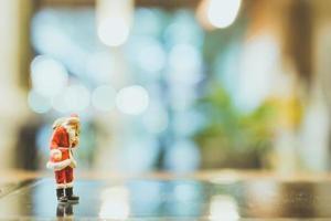 Miniatur-Weihnachtsmann, der auf Glas mit einem unscharfen Hintergrund steht foto