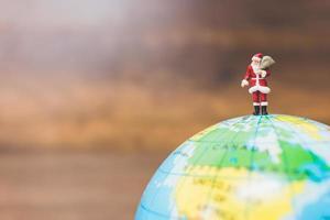 Miniatur-Weihnachtsmann, der Geschenke trägt, die auf einem Globus stehen foto