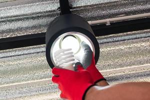 Paar Hände in roten Handschuhen, die eine Leuchtstofflampe durch eine LED-Lampe ersetzen foto