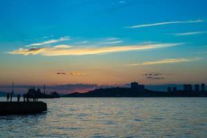 Seestück mit Schattenbild der Leute auf einem Pier mit buntem bewölktem Sonnenuntergang in Wladiwostok, Russland foto