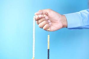 Hand des muslimischen Mannes, der Gebetsperlen auf blauem Hintergrund hält