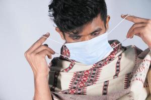 junger Mann, der chirurgische Gesichtsmaske aufsetzt
