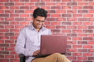 junger Mann, der Laptop benutzt, während er in einem Stuhl sitzt