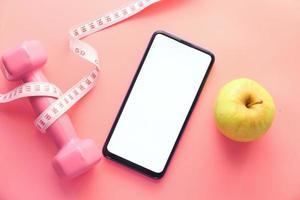 gesundes Diätkonzept mit Smartphone, Apfel und Hantel auf rosa Hintergrund foto