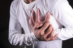 Mann hält Brust in Schmerzen