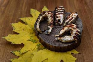 Fischsteaks gebraten auf dem Grill, der auf Baumstamm liegt foto